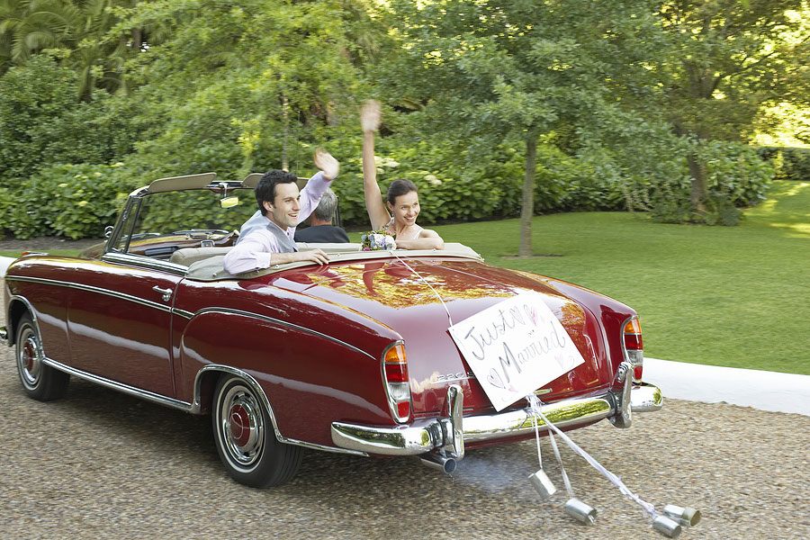 Bride and Groom waving in vintage convertible